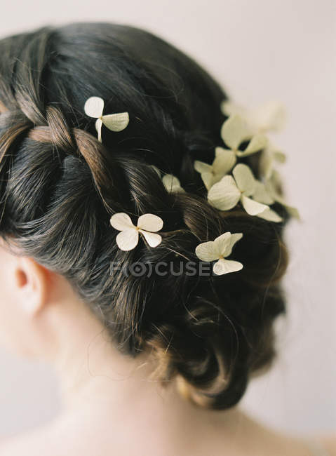 Braided hair with flower decoration — Stock Photo