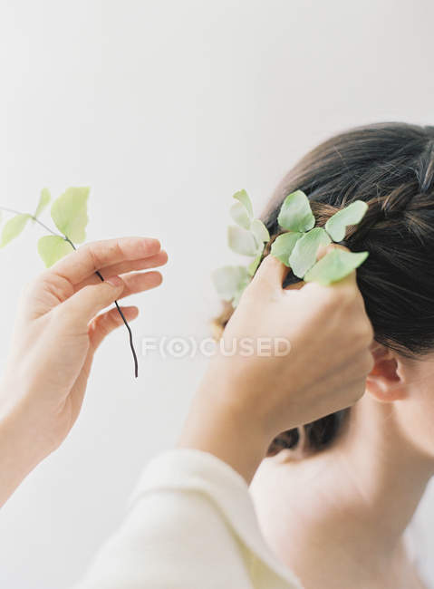 Hands adding leaves to braided updo — Stock Photo