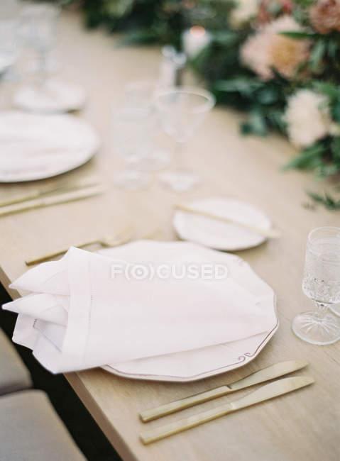 Teller mit Servietten und Geschirr — Stockfoto