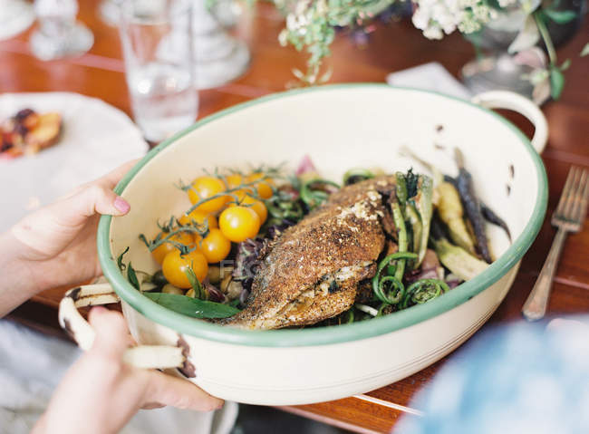 Female hands holding baked fish — Stock Photo