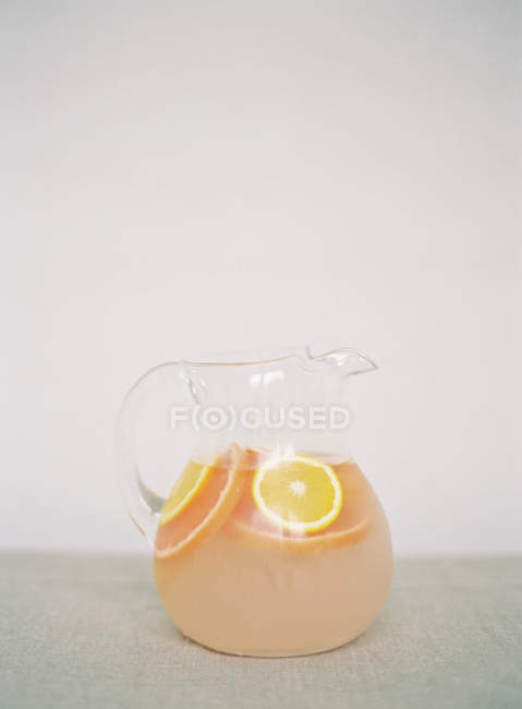 Pot avec boisson fraîche aux agrumes sur la table — Photo de stock