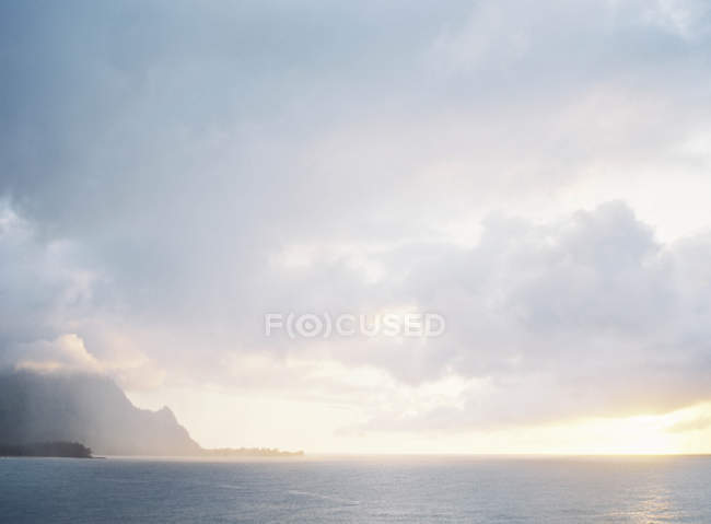 Distant island and clouds-cape — Stock Photo