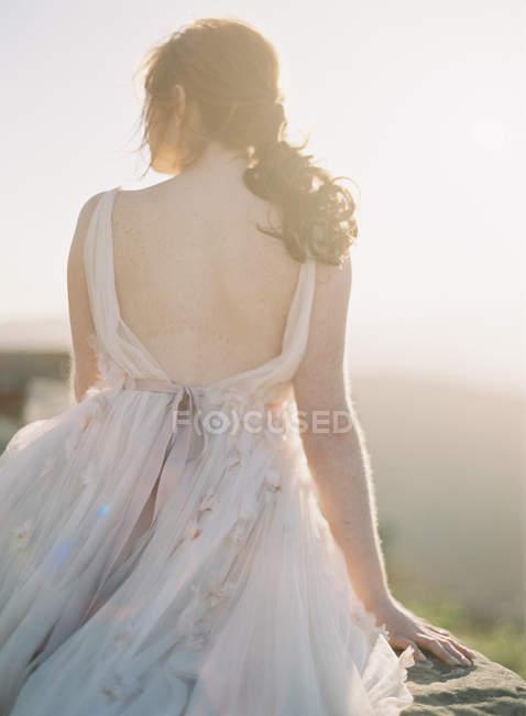 Femme assise en robe sur boulder — Photo de stock