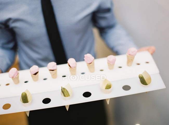Tray with ice cream cones and pickles — Stock Photo