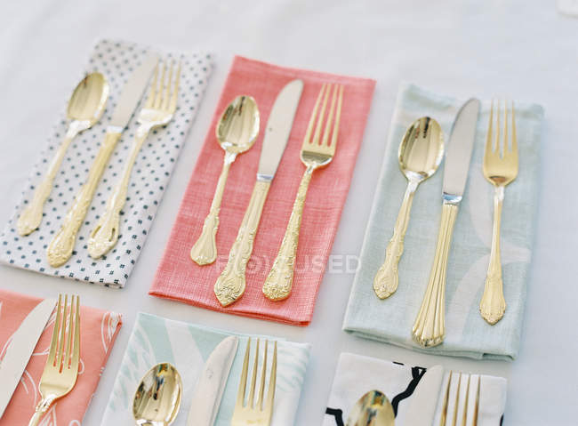 Cutlery on colorful patterned napkins — Stock Photo