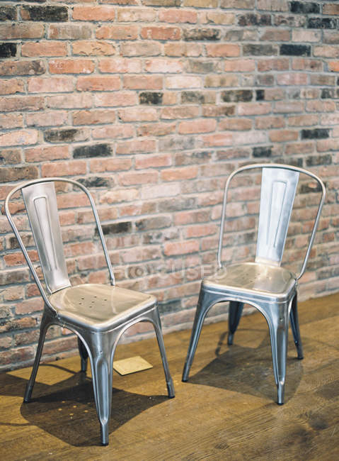 Metal chairs by brick wall — Stock Photo