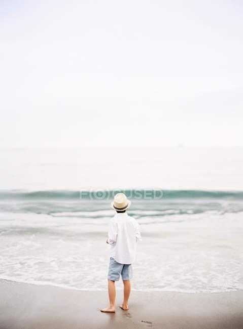 Вид сзади мальчик в шляпе против серфинг волны на пляже — стоковое фото