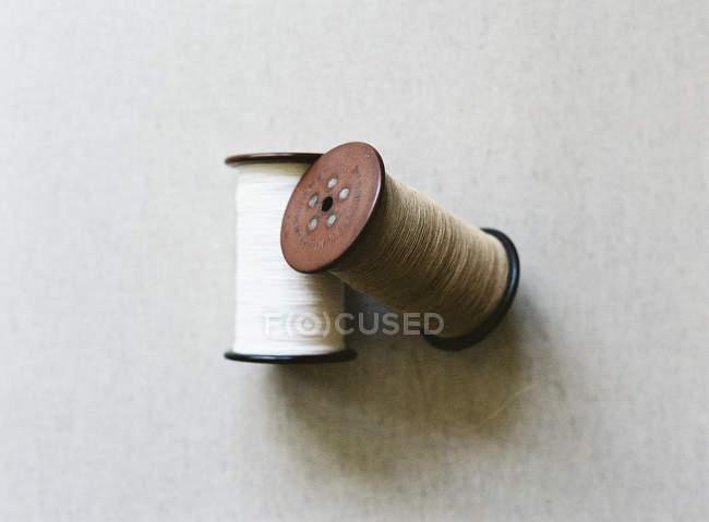 Белый и бежевый катушки ниток — стоковое фото