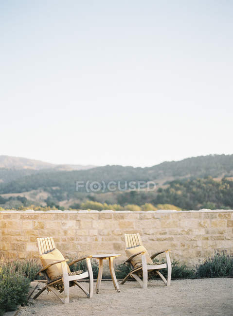 Chairs standing by stone fence — Stock Photo
