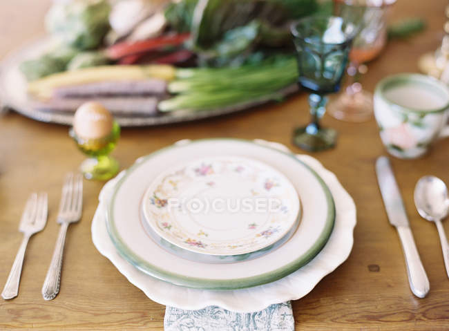 Stacked ceramic plates on setting table — Stock Photo