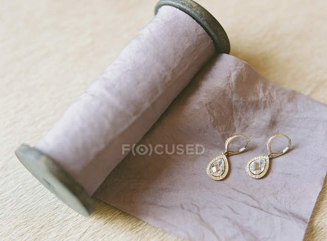 Elegant earrings on wrapping fabric — Stock Photo
