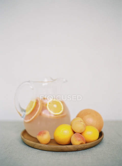 Jar with fresh citrus drink on table — Stock Photo