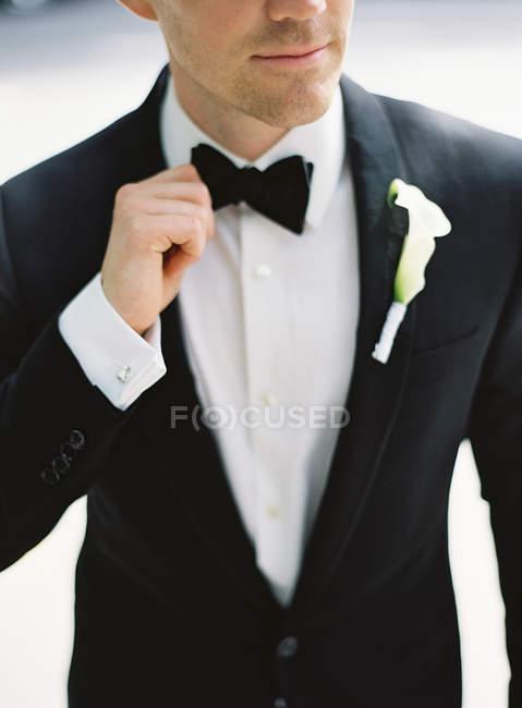 Man adjusting bow tie — Stock Photo