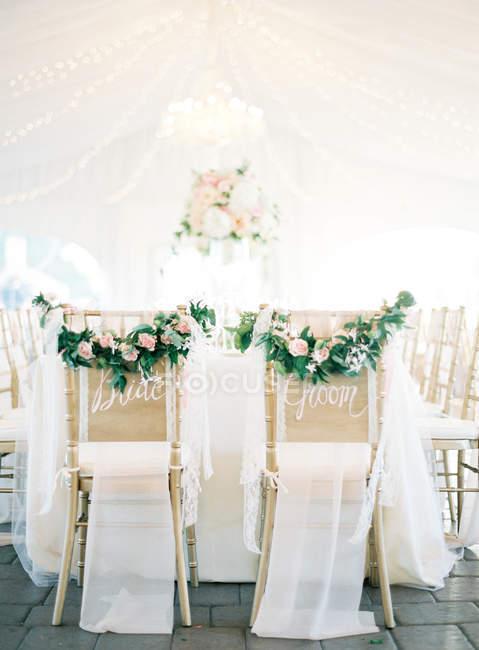 Chaises décorées de fleurs fraîches coupées — Photo de stock