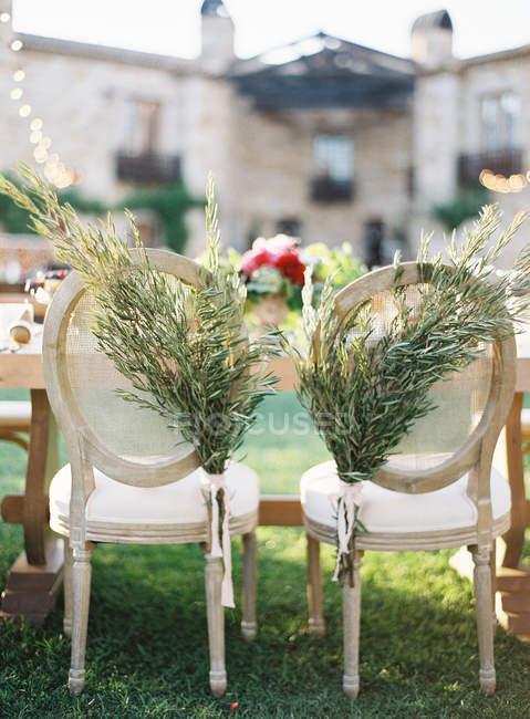 Chaises décorées avec des branches fraîches coupées — Photo de stock