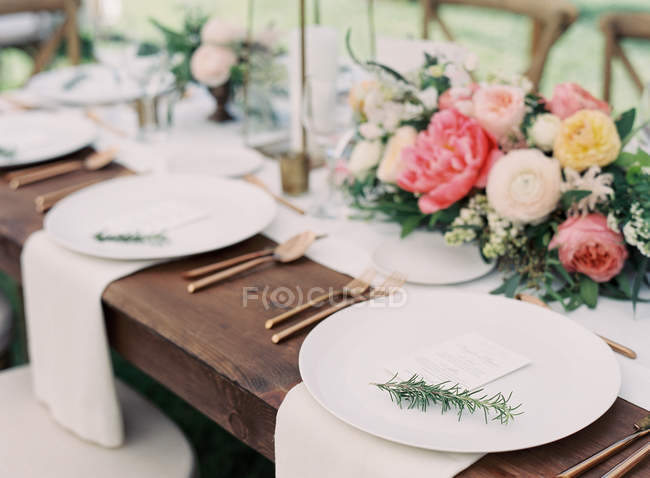 Floral arrangement on setting table — Stock Photo