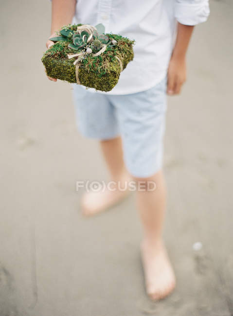 Male hand holding gift in floral wrapper — Stock Photo