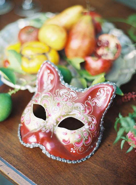 Karnevalsmaske und Teller mit frischen Früchten — Stockfoto