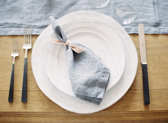 Table napkin on dinner plates — Stock Photo