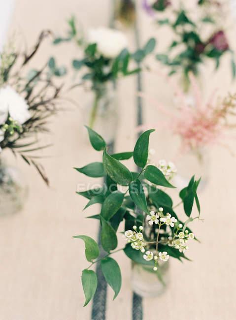 Букеты цветов в вазах и на столе — стоковое фото