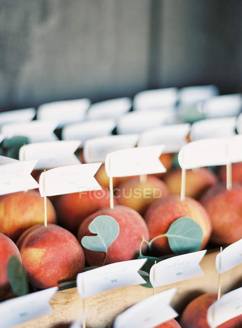 Fresh peaches with flags labels — Stock Photo