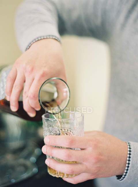 Man pouring drink into glass — Stock Photo
