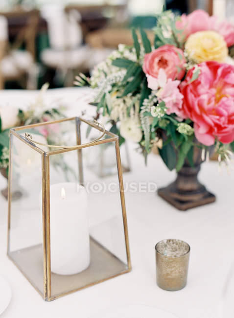 Bouquet in antique vase and candles — Stock Photo