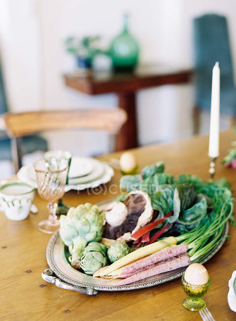 Artichokes and vegetables on table — Stock Photo