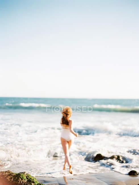 Красивая женщина бегает по пляжу — стоковое фото