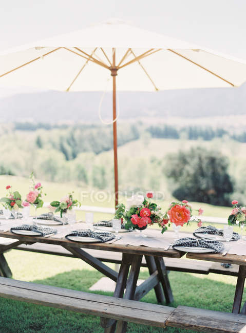 Wooden setting table decorated with flowers — Stock Photo