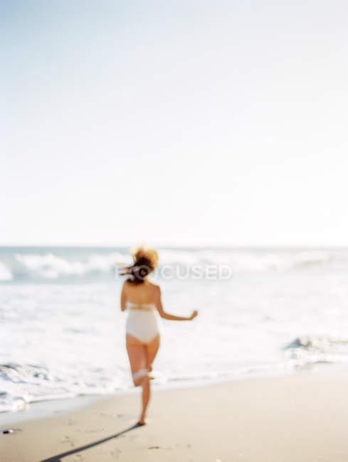 Hermosa mujer corriendo en la playa - foto de stock