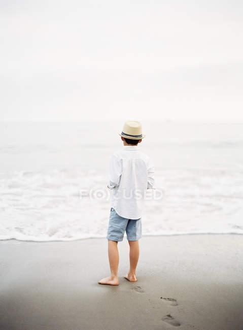 Visão traseira do menino de chapéu na praia — Fotografia de Stock