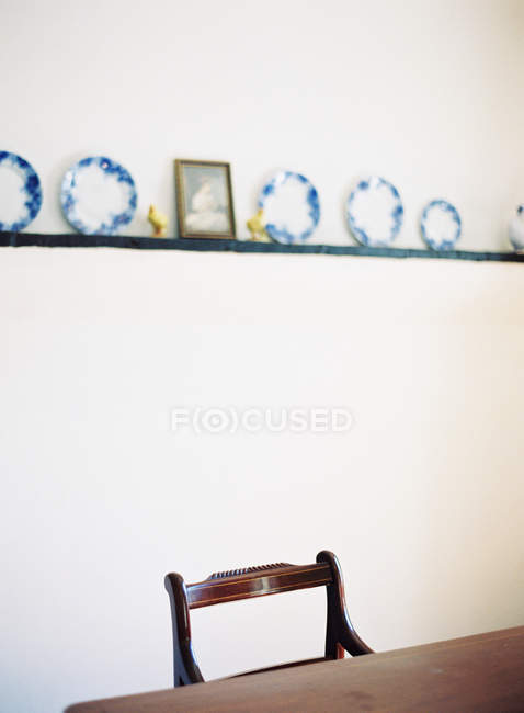 Chair and table under shelf with plates — Stock Photo