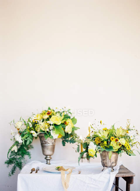 Bouquets of flowers in antique vases — Stock Photo