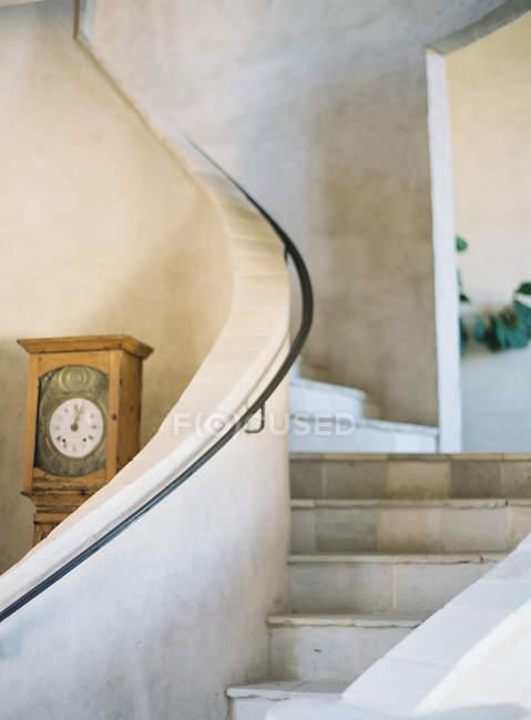Curva de escaleras con reloj - foto de stock