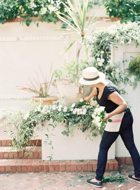 Rear view of woman in hat taking care of potted plants on wall — Stock Photo