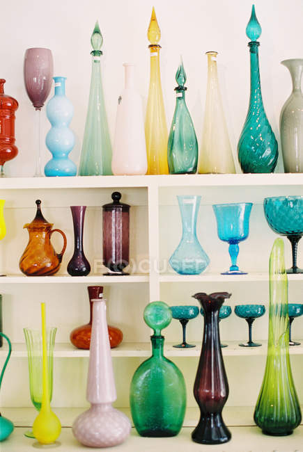 Colorful bottles and vases on wooden shelves — Stock Photo