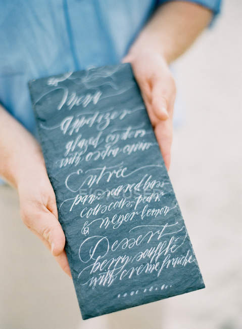Woman holding stone tablet with dinner menu — Stock Photo