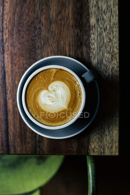 Cappuccino with heart on table — Stock Photo