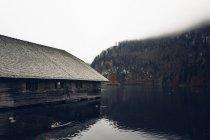 Casa in legno sulla riva del lago — Foto stock