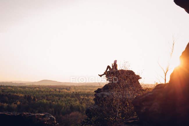 Mulher sentada na rocha e olhando para a floresta — Fotografia de Stock