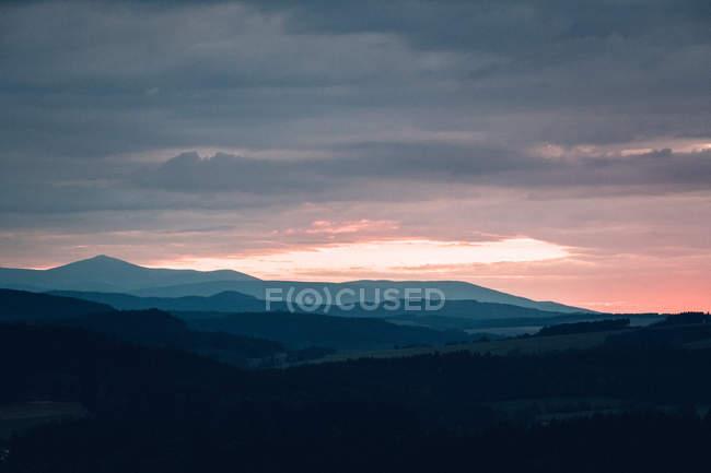 Paesaggio montuoso con il tramonto sullo sfondo — Foto stock