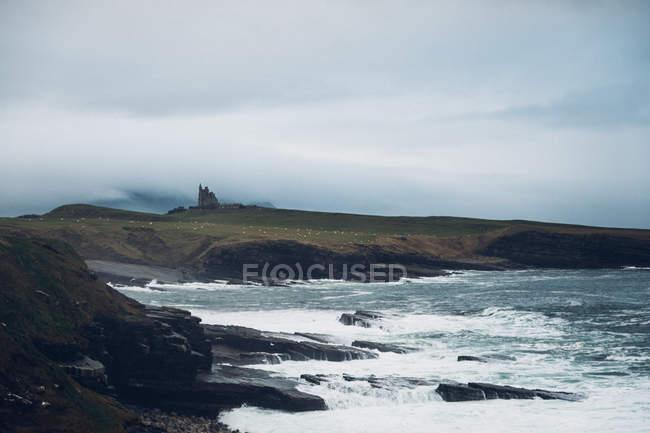 Praia rochosa com mar tempestuoso — Fotografia de Stock
