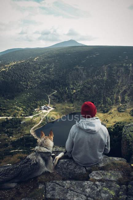 Junger Mann mit Hund sitzt am Rand der Klippe — Stockfoto
