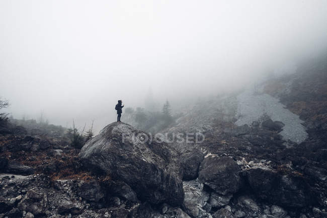 Man standing on top of large rock — Stock Photo