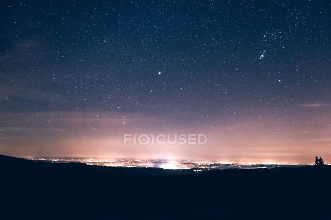Großstadt von Lichtern in der Nacht beleuchtet. — Stockfoto