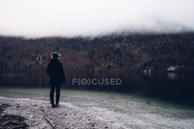 Человек, стоящий на берегу реки — стоковое фото