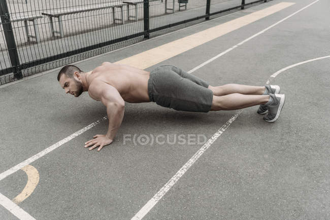 Handsome shirtless man doing push up at sports ground — Stock Photo