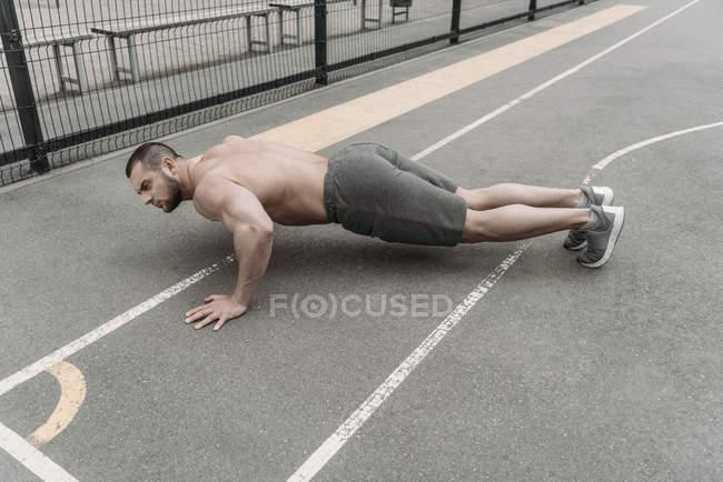 Uomo senza camicia bello facendo push up presso campo sportivo — Foto stock