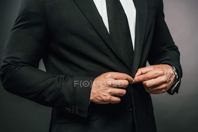 Cropped view of african american businessman in suit fixing button on dark background — Stock Photo